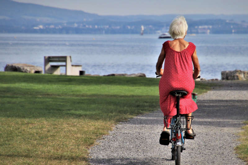 Senior citizen riding bike next to ocean